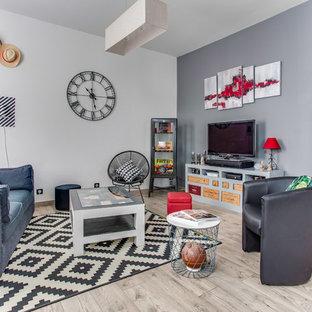 Idee per un grande soggiorno contemporaneo aperto con pavimento in laminato, stufa a legna, TV autoportante, pareti grigie, cornice del camino in metallo e pavimento grigio