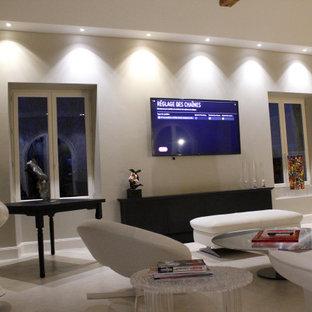 ボルドーの巨大なトランジショナルスタイルのおしゃれなLDK (ベージュの壁、トラバーチンの床、標準型暖炉、石材の暖炉まわり、壁掛け型テレビ、白い床) の写真