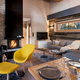Exemple d'un salon montagne ouvert avec un mur marron, un sol en bois brun, une cheminée d'angle, un manteau de cheminée en pierre, un téléviseur indépendant et un sol marron.