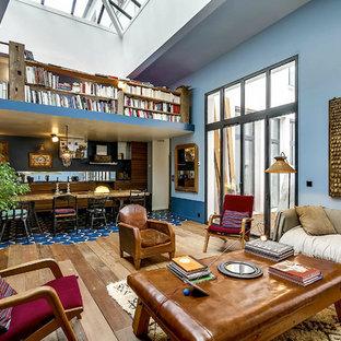 Idéer för stora eklektiska allrum med öppen planlösning, med blå väggar, mellanmörkt trägolv och ett bibliotek