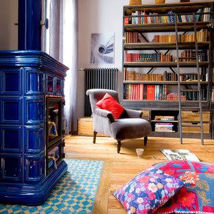 Imagen de biblioteca en casa ecléctica con paredes rosas, suelo de madera en tonos medios, marco de chimenea de baldosas y/o azulejos y estufa de leña