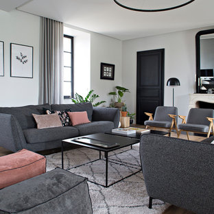 Cette image montre un salon traditionnel fermé avec une salle de réception, un mur blanc, un sol en bois brun et une cheminée standard.