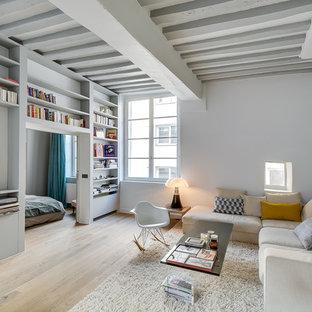 Immagine di un grande soggiorno nordico aperto con pareti bianche, parquet chiaro, libreria, nessun camino e nessuna TV