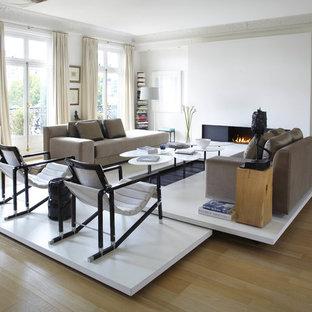 パリの大きい北欧スタイルのおしゃれなLDK (白い壁、淡色無垢フローリング、横長型暖炉、ライブラリー、テレビなし) の写真