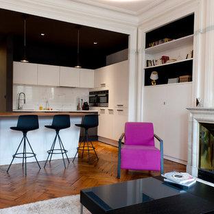 Cette image montre un salon avec une bibliothèque ou un coin lecture design de taille moyenne et ouvert avec un mur blanc, un sol en bois brun, une cheminée standard, un manteau de cheminée en pierre et aucun téléviseur.