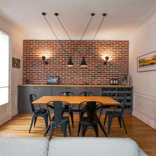 Exemple d'un salon industriel avec un mur blanc, un sol en bois brun et un sol marron.
