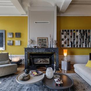 Cette image montre un grand salon bohème ouvert avec une salle de réception, un mur jaune, un sol en bois brun, une cheminée standard, un manteau de cheminée en pierre et aucun téléviseur.