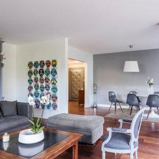 Réalisation d'un grand salon design ouvert avec une salle de réception, un mur blanc, un sol en bois brun, aucune cheminée et aucun téléviseur.