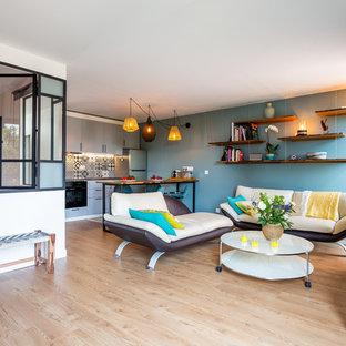 Exemple d'un salon tendance ouvert avec un mur bleu, un sol en bois brun, un téléviseur indépendant et un sol beige.