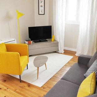 Cette photo montre un salon tendance de taille moyenne et fermé avec un mur beige, un sol en bois brun, aucune cheminée et un téléviseur indépendant.