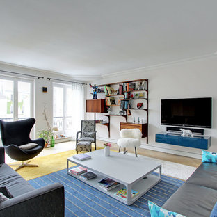 Cette photo montre un salon avec une bibliothèque ou un coin lecture tendance de taille moyenne et fermé avec un mur blanc, un sol en bois clair, un téléviseur fixé au mur et aucune cheminée.