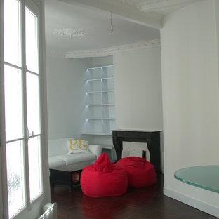 Immagine di un soggiorno design di medie dimensioni e chiuso con libreria, pareti bianche, parquet scuro, camino classico, cornice del camino in pietra, parete attrezzata e pavimento rosso