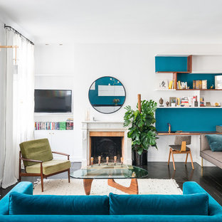 Aménagement d'un salon avec une bibliothèque ou un coin lecture contemporain de taille moyenne et ouvert avec un mur bleu, un sol en bois peint, une cheminée standard, un manteau de cheminée en pierre, un téléviseur fixé au mur et un sol noir.