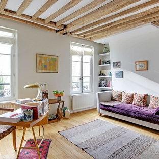 Exemple d'un salon méditerranéen avec un mur blanc et un sol en bois clair.