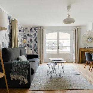 Réalisation d'un salon design avec un mur blanc, un sol en bois clair, une cheminée d'angle, un téléviseur fixé au mur et un sol beige.