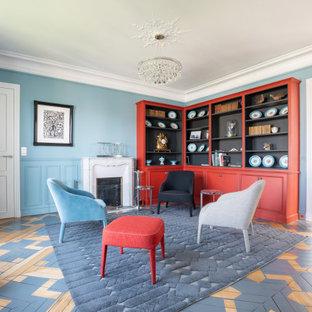 Inspiration pour un grand salon avec une bibliothèque ou un coin lecture traditionnel fermé avec un mur bleu, un sol en bois peint, une cheminée standard, un manteau de cheminée en pierre, un sol multicolore et boiseries.