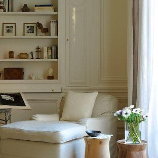 Idées déco pour un salon avec une bibliothèque ou un coin lecture beige et marron classique fermé et de taille moyenne avec un sol en bois clair, aucune cheminée, aucun téléviseur, un mur blanc et un sol beige.