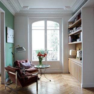Idée de décoration pour un salon avec une bibliothèque ou un coin lecture design de taille moyenne et ouvert avec un mur vert, un sol en bois clair, aucune cheminée et aucun téléviseur.