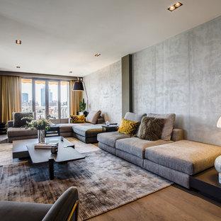 Exemple d'un salon tendance ouvert avec un mur gris, un sol en bois brun, un téléviseur encastré et un sol marron.