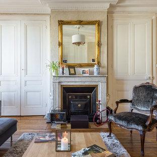 Cette image montre un grand salon bohème fermé avec un mur beige, un sol en bois brun, une cheminée standard, un manteau de cheminée en pierre et aucun téléviseur.