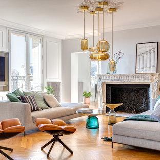 Réalisation d'un salon tradition de taille moyenne et ouvert avec une cheminée standard, un sol marron, un mur blanc, un sol en bois clair, un manteau de cheminée en pierre, aucun téléviseur et une salle de musique.