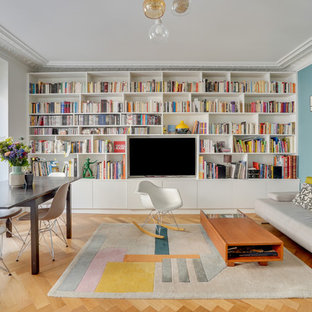 Cette photo montre un salon tendance de taille moyenne avec un mur bleu, un téléviseur fixé au mur, un sol marron et aucune cheminée.