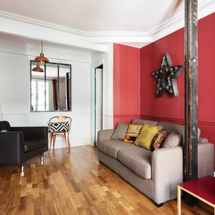 Diseño de salón para visitas cerrado, bohemio, de tamaño medio, sin chimenea y televisor, con paredes rojas y suelo de madera clara