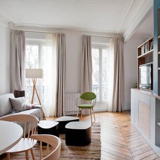 Cette photo montre un salon tendance avec un mur blanc, un sol en bois brun et un téléviseur fixé au mur.