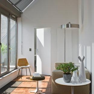 Aménagement d'un salon contemporain ouvert avec une salle de réception, un mur blanc, un sol en bois brun, aucune cheminée et aucun téléviseur.
