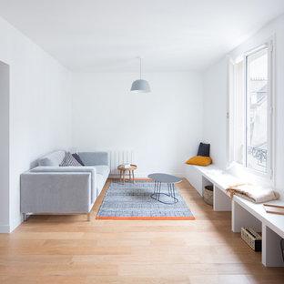 Idée de décoration pour un salon nordique fermé et de taille moyenne avec une salle de réception, un mur blanc, un sol en bois clair, aucun téléviseur, aucune cheminée et un sol marron.