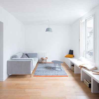 Mid-sized danish formal and enclosed light wood floor and brown floor living room photo in Paris with white walls, no tv and no fireplace