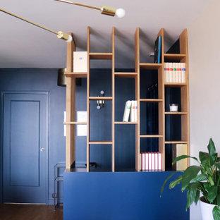 Esempio di un soggiorno moderno di medie dimensioni e aperto con libreria, pareti blu e pavimento in laminato