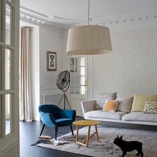 Idées déco pour un salon scandinave avec un sol en bois foncé et un mur beige.