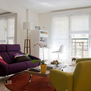 Cette image montre un salon bohème ouvert et de taille moyenne avec un mur beige, un sol en bois clair, aucune cheminée et aucun téléviseur.