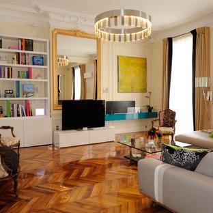 パリの広いトラディショナルスタイルのおしゃれな独立型リビング (ベージュの壁、淡色無垢フローリング、吊り下げ式暖炉、木材の暖炉まわり、据え置き型テレビ) の写真