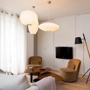 Réalisation d'un salon design avec un mur gris, un sol en bois brun, un téléviseur fixé au mur et un sol marron.