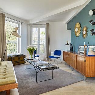 Cette image montre un salon vintage fermé avec une salle de réception, un mur multicolore, un sol en bois clair, aucune cheminée, aucun téléviseur et un sol beige.