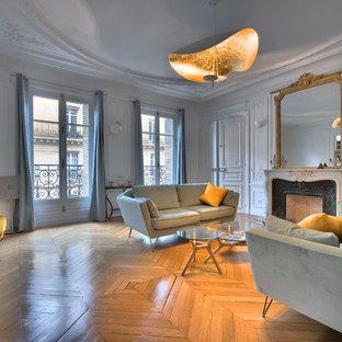 Aménagement d'un grand salon classique fermé avec un mur blanc, un sol en bois brun, une cheminée standard, un sol marron, un manteau de cheminée en pierre et aucun téléviseur.
