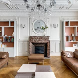 Aménagement d'un grand salon avec une bibliothèque ou un coin lecture classique fermé avec un mur blanc, un sol en bois brun, une cheminée standard, un manteau de cheminée en pierre et aucun téléviseur.