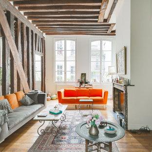 Cette image montre un grand salon design ouvert avec un mur blanc, un manteau de cheminée en brique, un sol marron, un sol en bois clair, une cheminée double-face et un plafond en poutres apparentes.
