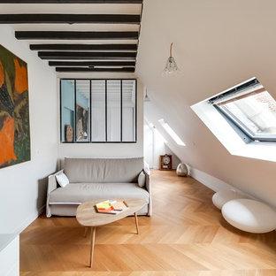 Réalisation d'un salon design de taille moyenne avec un sol en bois brun, un mur blanc, aucune cheminée et aucun téléviseur.