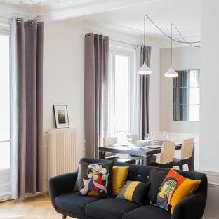 Réalisation d'un salon design ouvert et de taille moyenne avec un sol en bois brun, un mur blanc, aucune cheminée et aucun téléviseur.