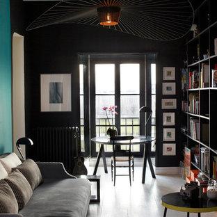 Réalisation d'un salon avec une bibliothèque ou un coin lecture design fermé et de taille moyenne avec un mur noir, un sol en bois peint, aucune cheminée et aucun téléviseur.