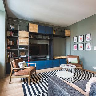 Cette image montre un salon avec une bibliothèque ou un coin lecture design de taille moyenne et fermé avec un mur vert, un sol en bois clair, aucune cheminée et un téléviseur fixé au mur.