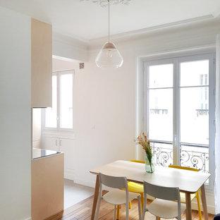 Modelo de salón abierto y machihembrado, actual, pequeño, con paredes blancas y suelo de madera en tonos medios