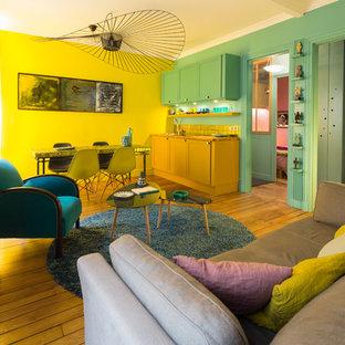 Idée de décoration pour un salon vintage de taille moyenne et ouvert avec un mur jaune, un sol en bois brun, aucune cheminée et aucun téléviseur.