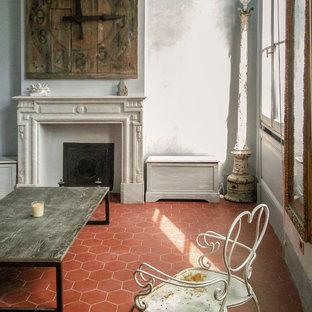 Ejemplo de biblioteca en casa abierta, clásica renovada, grande, sin televisor, con paredes beige, suelo de baldosas de terracota, chimenea tradicional, marco de chimenea de piedra y suelo naranja