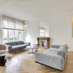 Aménagement d'un salon contemporain ouvert avec une salle de réception, un mur blanc, un sol en bois clair, une cheminée standard, un manteau de cheminée en pierre, aucun téléviseur et un sol beige.