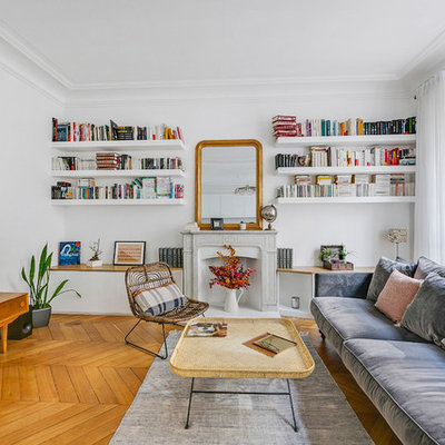 Large danish open concept medium tone wood floor and brown floor living room library photo in Paris with white walls, a standard fireplace, a stone fireplace and a tv stand