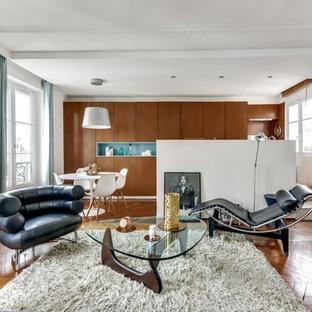 Exemple d'un salon tendance ouvert avec un mur blanc, un sol en bois brun, un téléviseur fixé au mur et un sol marron.